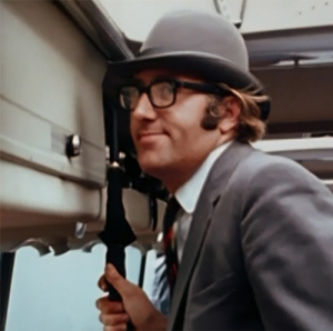 Resplendent in a smart gray blazer and striped tie, Mal Evans is already dressed for the role of Maxwell Edison as he rides the Magical Mystery Tour bus.